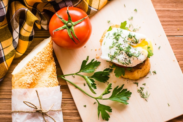 Sandwich with poached egg, tomato, baguette and parsley on a cutting board. top view