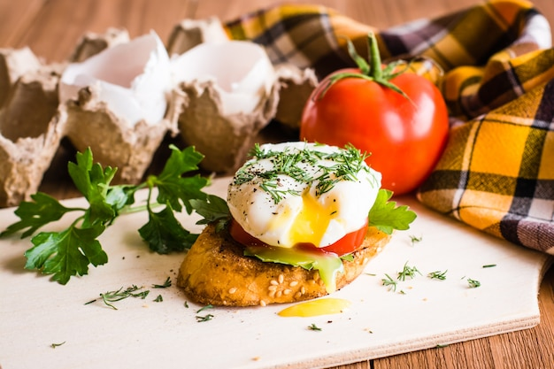 Sandwich with poached egg, tomato and egg shells