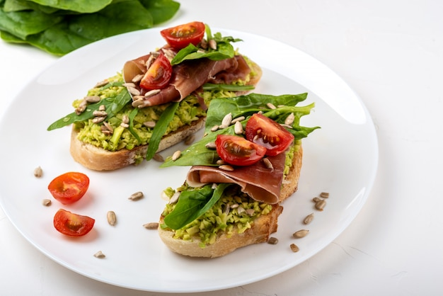 Sandwich with prosciutto, jamon, tomatoes and avocado