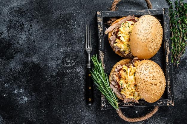 풀드 포크 고기와 코울슬로 샐러드를 곁들인 샌드위치. 검은 배경. 평면도. 공간을 복사합니다.