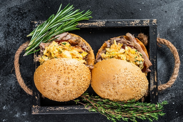 풀드 포크 고기와 코울슬로 샐러드를 곁들인 샌드위치. 검은 배경. 평면도. 프리미엄 사진