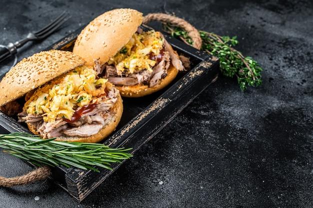Сэндвич с тушеной свининой и салатом из капусты. чернить