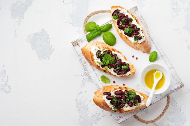 Сэндвич с красной фасолью, чесноком, оливковым маслом и творогом на белой поверхности