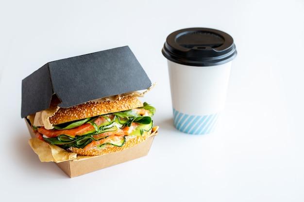 赤い魚、チーズ、ルッコラ、アボカド、キュウリのサンドイッチ。魚と一緒にバーガー。持ち帰り用の食品。宅配食品。サンドイッチにはコーヒーが詰められています。コーヒーとテイクアウト。スタイリッシュな食品の包装