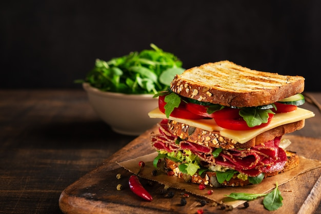 Sandwich with salami, cheese and fresh vegetables on rustic wooden cutting board