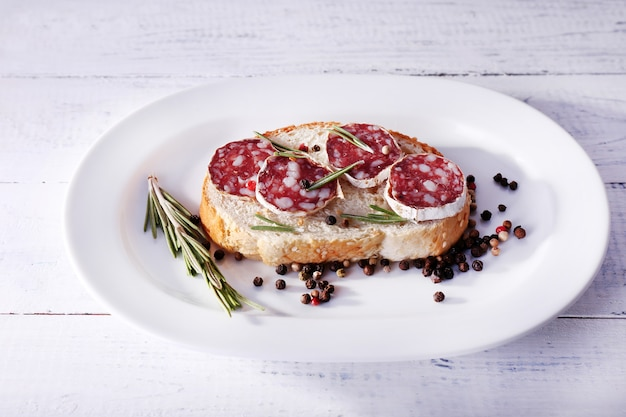 Sandwich with salami on plate on wooden