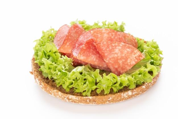 Сэндвич с колбасой салями на белом фоне.