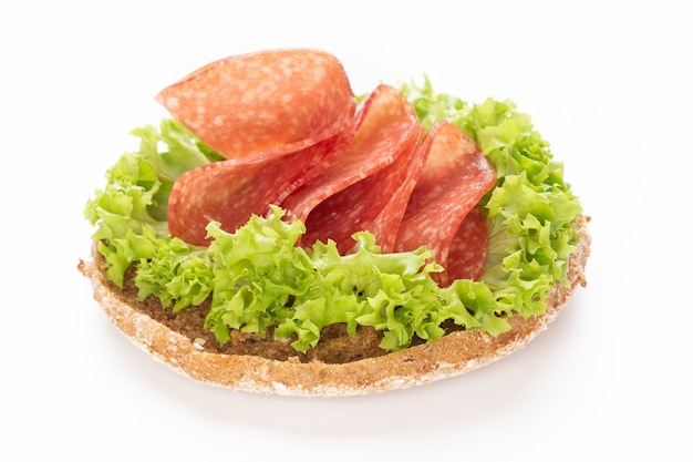Sandwich with salami sausage on white surface.
