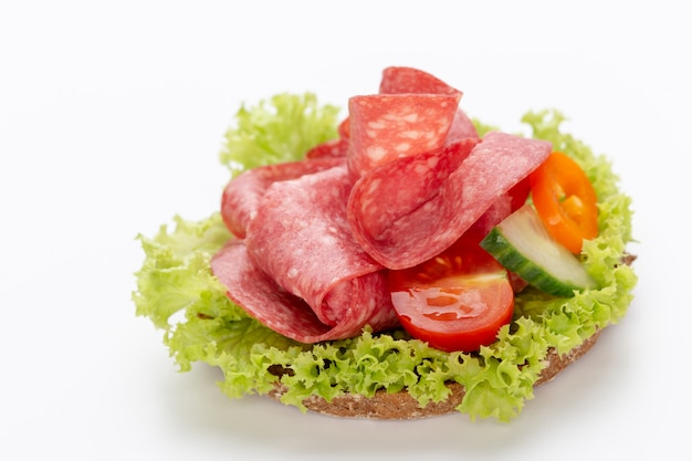 Sandwich with salami sausage on white.