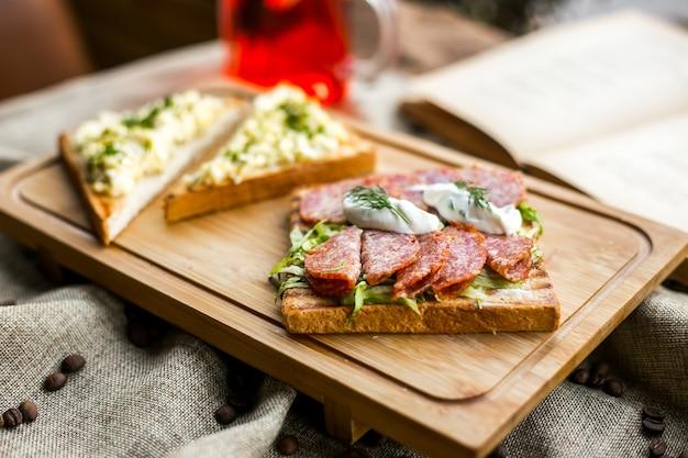 Бутерброд с тостами из салями, салат, колбаса, сметана, укроп, вид сбоку