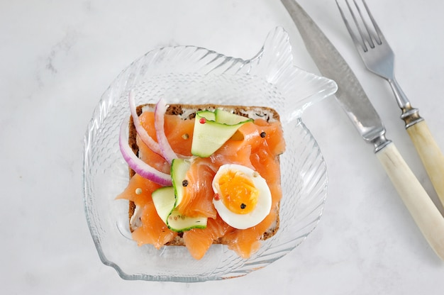 Sandwich with salmon, cucumber, egg and onion