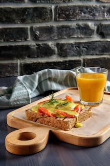 Sandwich with salmon, melted cheese and spicy sauce and a glass of orange juice