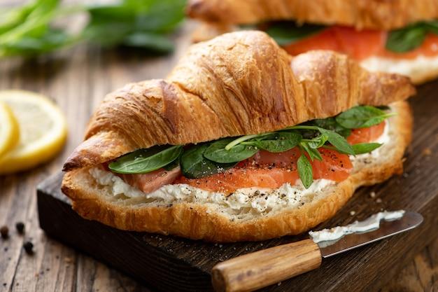 Бутерброд с лососем, шпинатом и сливочным сыром на деревянной доске, выборочный фокус, крупный план