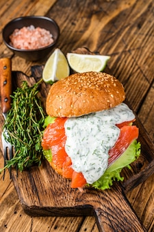 Sandwich with salted fish salmon, avocado, burger bun, mustard sauce and iceberg salad. wooden background. top view.
