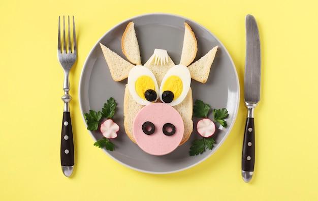 노란색 표면에 재미있는 황소 모양의 소시지와 계란 샌드위치, 어린이를위한 요리 아이디어, 상위 뷰
