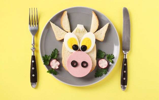 Sandwich with sausage and egg in the shape of a funny bull on yellow surface, culinary idea for children, top view