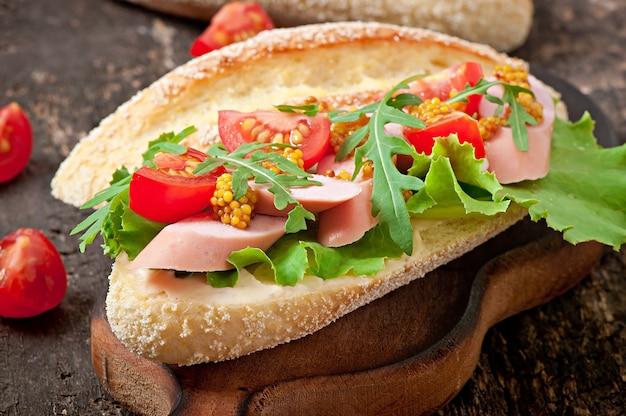 Бутерброд с колбасой, листьями салата, помидорами и рукколой на старой деревянной поверхности