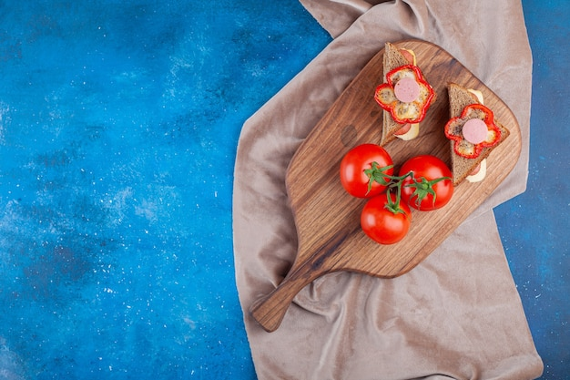 Sandwich with sausage and whole tomatoes on cutting board on pieces of fabric on blue.