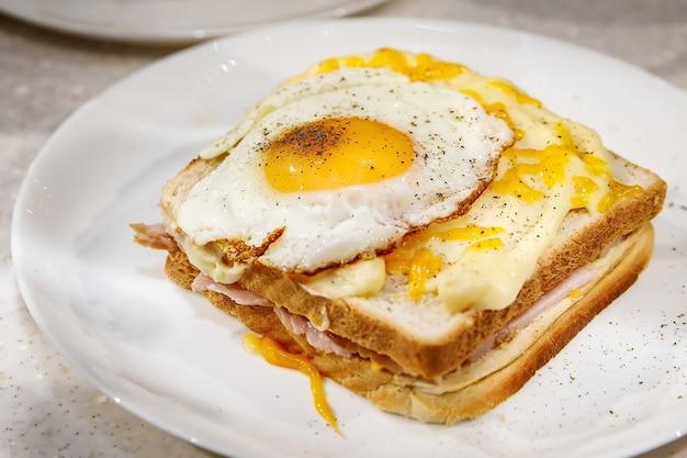 白い皿にスクランブルエッグのサンドイッチ。朝の朝食。
