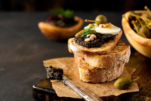 モッツァレラチーズとタプナードのスライス、暗い素朴なテーブルの背景にケーパーとサンドイッチ。伝統的なプロヴァンス料理。セレクティブフォーカス