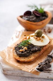 モッツァレラチーズとタプナードのスライス、ライトグレーの素朴なテーブルの背景にケーパーのサンドイッチ。伝統的なプロヴァンス料理。セレクティブフォーカス