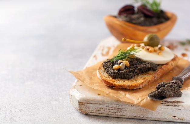 Сэндвич с ломтиком сыра моцарелла и тапенадом, каперсами на светло-сером деревенском фоне стола. традиционное блюдо прованса. выборочный фокус