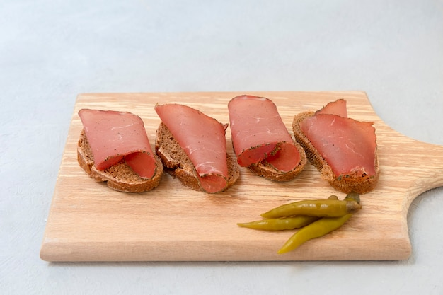 얇게 썬 말린 고기를 넣은 샌드위치는 중성 회색 배경의 커팅 보드에 제공됩니다.