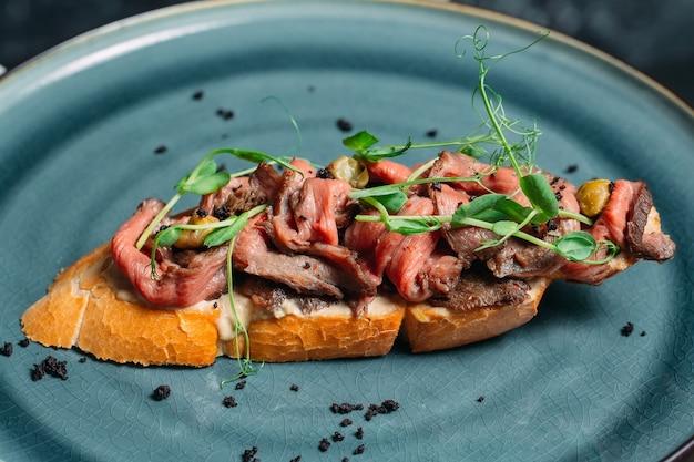 水色のエレガントなプレートにおいしいサーモンとハーブのスライスとサンドイッチ
