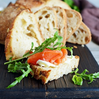 Sandwich with slightly salted salmon, arugula, seeds and cottage cheese on the board