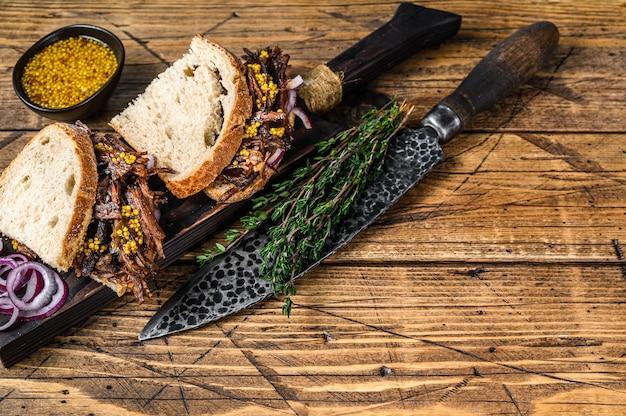흰 빵에 느린 훈제 쇠고기 양지머리 고기를 곁들인 샌드위치. 나무 배경입니다. 평면도. 공간을 복사합니다.