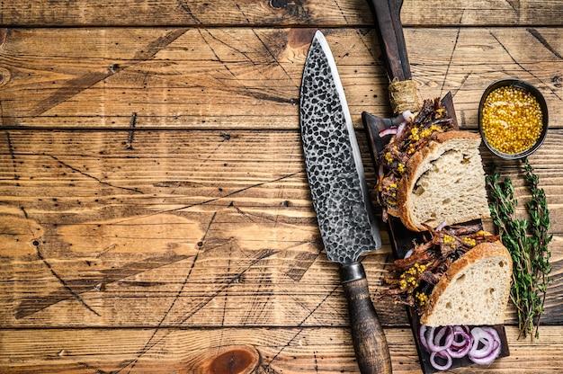 흰 빵에 천천히 훈제 뽑아 돼지 고기 샌드위치. 나무 배경입니다. 평면도. 공간을 복사하십시오.