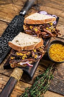 흰 빵에 천천히 훈제 돼지고기를 곁들인 샌드위치. 나무 배경입니다. 평면도.