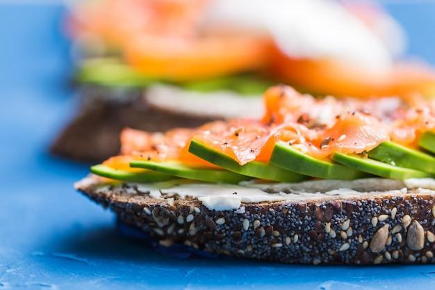 훈제 연어와 아보카도가 들어간 샌드위치. 건강한 영양에 대한 개념.