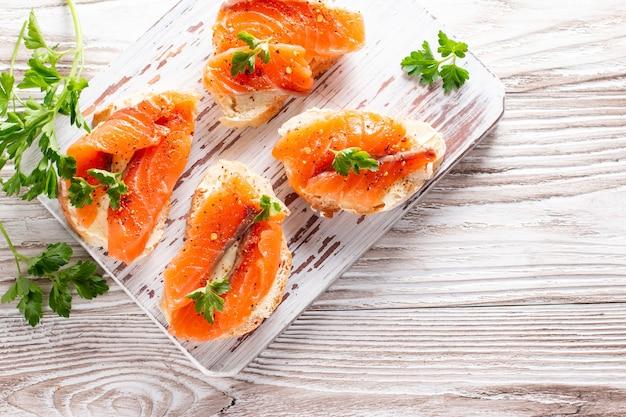 Сэндвич с копченым лососем и маслом на деревянной доске, горизонтальный, вид сверху