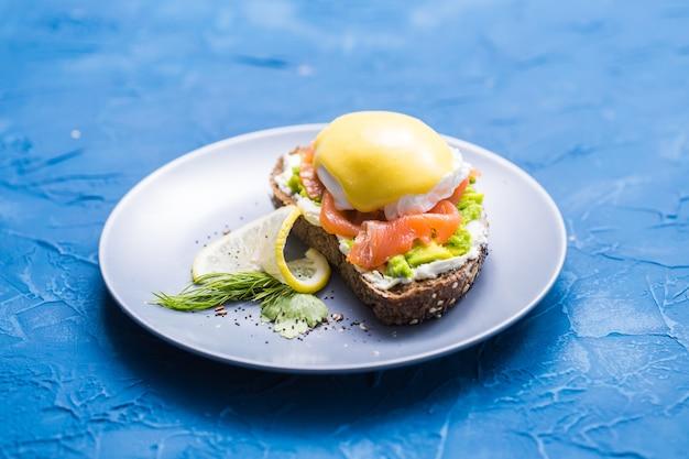 훈제 연어, 계란, 파란색 배경에 아보카도와 샌드위치. 건강한 영양에 대한 개념.