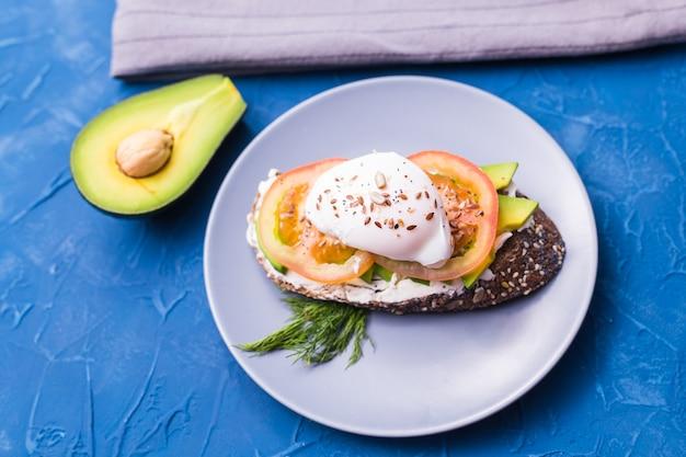훈제 연어, 계란, 파란색 배경, 평면도에 아보카도와 샌드위치. 건강을위한 개념