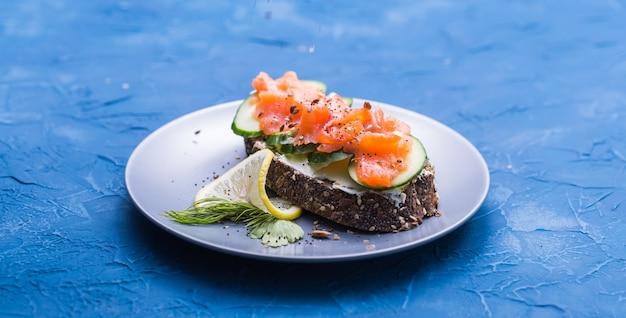 훈제 연어, 계란, 파란색 표면에 아보카도와 샌드위치 클로즈업. 건강한 영양 개념