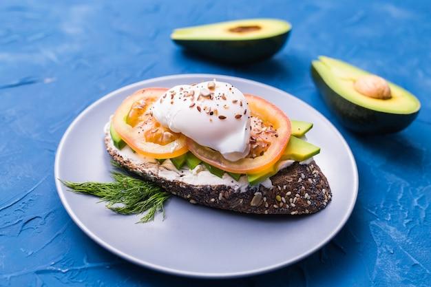 파란색 표면에 훈제 연어, 계란, 아보카도와 샌드위치. 건강한 영양에 대한 개념.