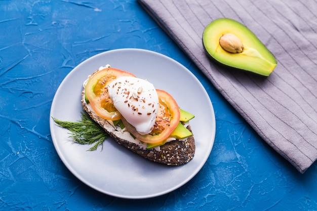 훈제 연어, 계란, 파란색 표면, 상위 뷰에 아보카도와 샌드위치. 건강을위한 개념