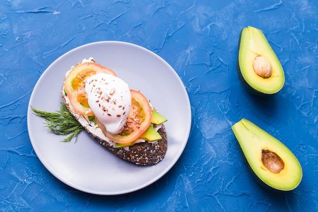 훈제 연어, 계란, 파란색 벽, 평면도에 아보카도와 샌드위치. 건강한 영양에 대한 개념.