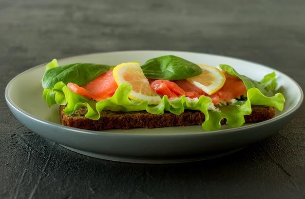スモークサーモンの格子とレモンのサンドイッチ。美味しくて健康的な食事のコンセプト。皿の上の食べ物