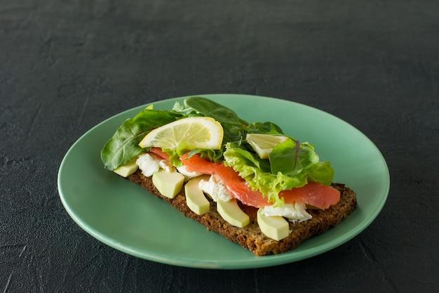スモークサーモンのソフトチーズ、格子、アボカドのサンドイッチ。美味しくて健康的な食事のコンセプト。皿の上の食べ物。