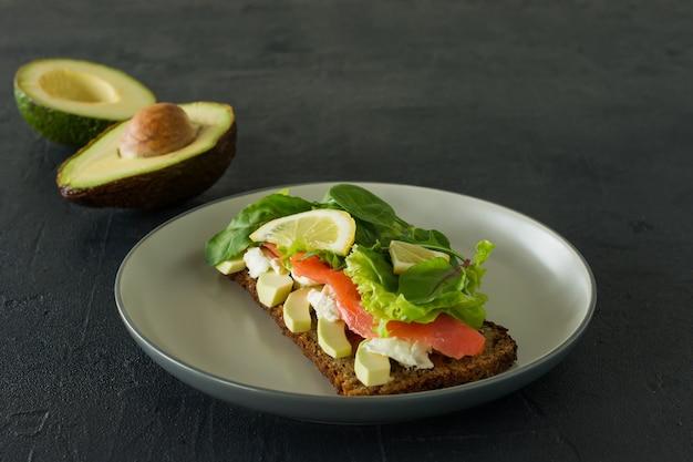 スモークサーモンのソフトチーズ、格子、アボカドのサンドイッチ。美味しくて健康的な食事のコンセプト