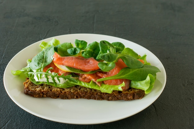 スモークサーモンのソフトチーズ、格子、レモンのサンドイッチ。美味しくて健康的な食事のコンセプト。皿の上の食べ物。