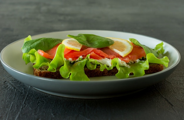 スモークサーモンのソフトチーズ、格子、レモンのサンドイッチ。美味しくて健康的な食事のコンセプト。