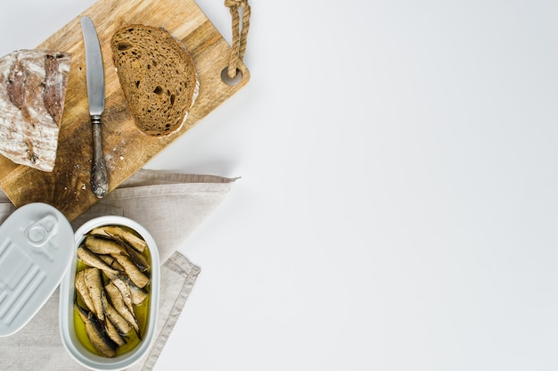Sandwich with smoked sprats in oil, ceramic jar, wooden cutting board with black bread.