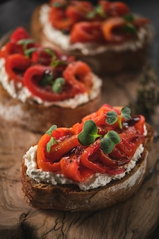 Sandwich with soft cheese and baked red bell pepper on a wooden board  italian bruschetta antipasti