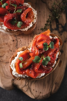 Sandwich with soft cheese and baked red bell pepper on a wooden board.  italian bruschetta antipasti