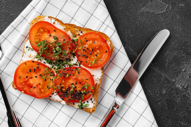 Sandwich with soft cheese and sliced tomatoes