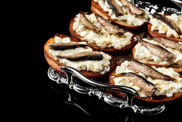 Бутерброд со шпротами, яйцами и майонезом на черной поверхности.